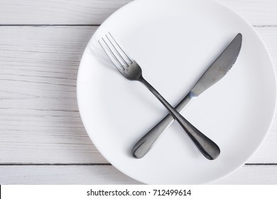Empty plate with crossed fork and knife. Dish and cutlery top view on white wood table background