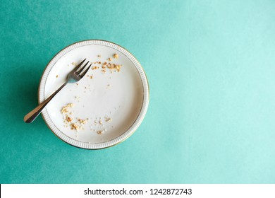 Empty plate with crumbs after eating on a green background. The concept of the end of the holiday or celebration. Nearby place for text.