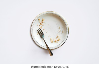 Empty plate with crumbs after eating on a white background. The concept of the end of the holiday or celebration.