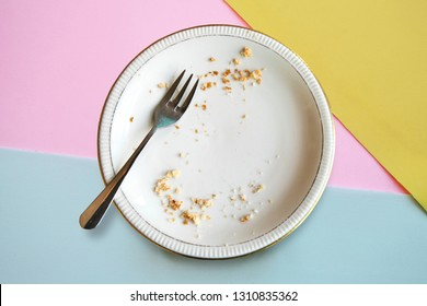 Empty plate with crumbs after eating on a color background. The concept of the end of the holiday or celebration.