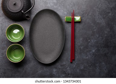 Empty plate, cup, teapot and chopsticks over black textured table. Japanese food template. Top view with copy space. Flat lay
