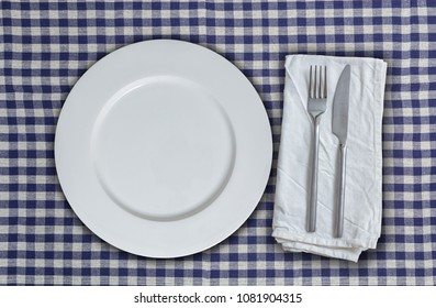 Empty plate and cutlery on blue-white checkered cloth.
