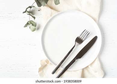 An empty plate and cutlery on a white table.