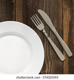 Empty Plate And Cutlery On The Wooden Table.