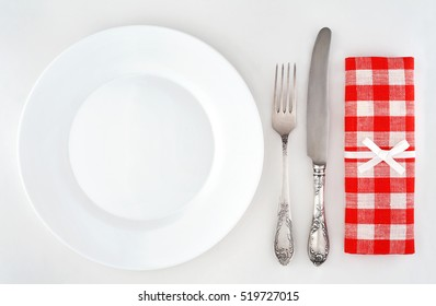Empty plate with cutlery and red checkered napkin. Overhead view.