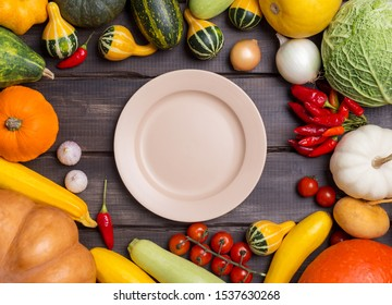 Empty plate with different kinds of harvest vegetables on dark wooden background. Pumpkin, cabbage, onion, tomatoes, garlic, pepper around the empty plate. Concept of harvest autumnal serving plate