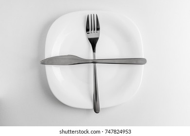 An empty plate, fork and knife lie crosswise on a white background. The dish did not like table etiquette