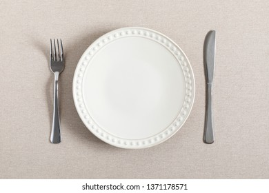 Empty plate, fork and knife on beige background linen tablecloth. Flat lay, top view, copy space