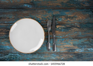 Empty plate with fork and knife on colored wooden background, top view, copy space, mock-up