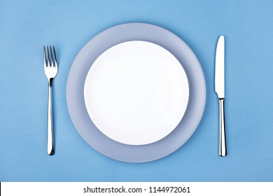 Empty plate with fork and knife. Setting table, top view.