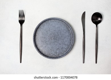 empty plate, fork, spoon and knife on a gray concrete background. view from above