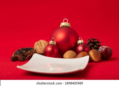 Empty plate in front of decorations for Christmas with nuts and Christmas tree scoops