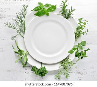 Empty plate with herbs on wooden table