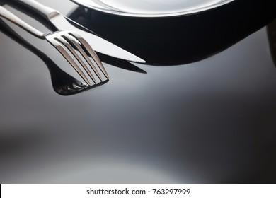 Empty plate with knife and fork on a black background.