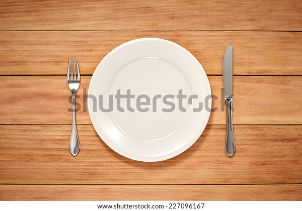 Empty Plate, Knife and Fork on wooden background. Top View Text Space