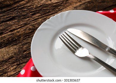 empty plate with knife and fork and red napkin