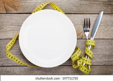 Empty plate with measure tape, knife and fork. Diet food on wooden table