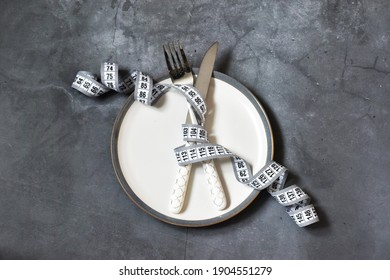 Empty plate with measuring tape, knife and fork on gray concrete background. Diet. Healthy food, weight loss. Copy space. Flat lay.