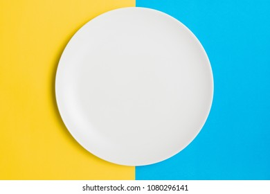 Empty plate on a contrasting yellow and blue background.