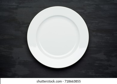 Empty plate on dark black wooden background. Top view with copy space