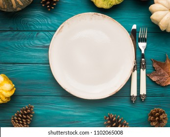Empty plate on Moody green autumn background with pumpkin and yellow leaves. Fall food still life flat lay. Copy space frame