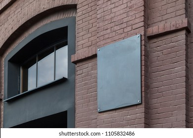 An empty plate on an old building of a dark brick factory. Mockup.