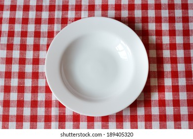 empty plate on a red and white tablecloth