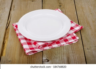 Empty plate on red-white checkered tablecloth in an old wooden table
