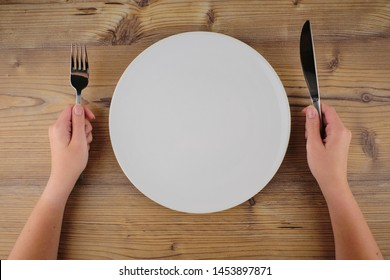 empty plate on the table and Cutlery in hand top view