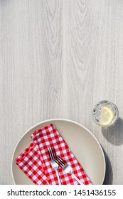 Empty plate on table with glass of sparkling water.Concept photo with empty space for text.