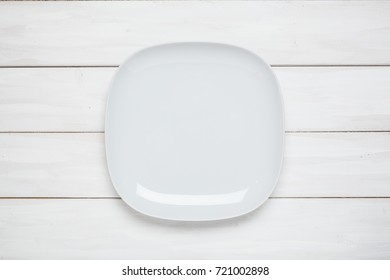 Empty plate on white plank wooden background with copy space. Top view. Montage product