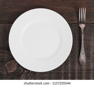 Empty plate on white wooden table