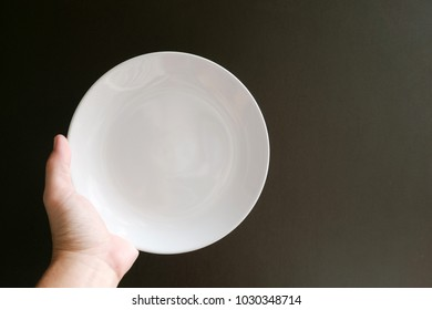 Empty plate on the your hand in black backgroud