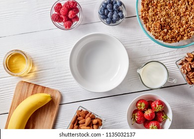 Empty plate, organic granola, banana, honey, milk, berries and almonds on a white wooden table with copy space. Ingredients for a healthy breakfast, step by step recipe. Top view