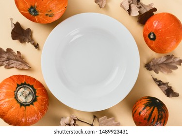 Empty plate with pumpkin and dry leaves Autumn menu concept