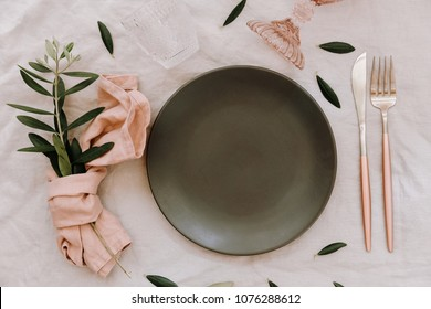 Empty plate with rustic decorations. Wedding table set with linen napkin and olive branch. Top view