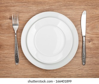 Empty plate and silverware set on wooden table