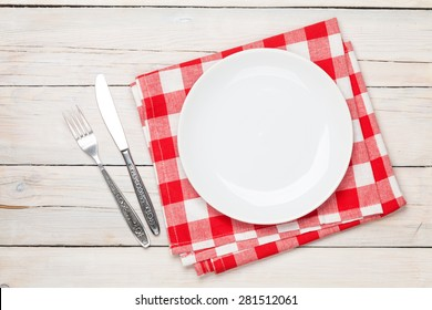 Empty plate, silverware and towel over wooden table background. View from above with copy space