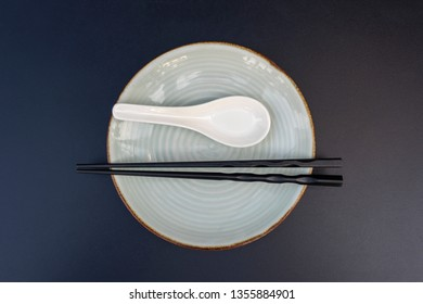 Empty plate, spoon and chopsticks on black table in asian restaurant, close up, top view. Table setting