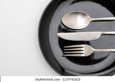 empty plate spoon fork and knife isolated on white background