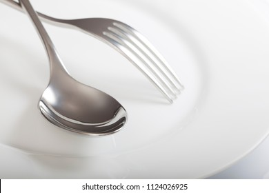 Empty plate with spoon and fork on a white background.
