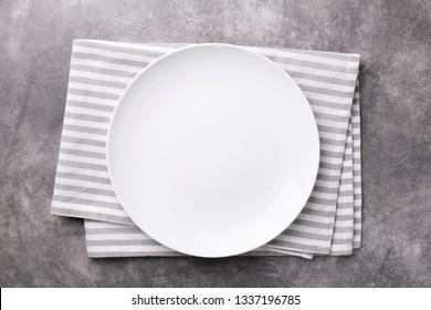 Plaque vide avec serviette rayée sur fond gris en pierre. Vue de dessus.