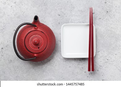 Empty plate, teapot with herbal tea and chopsticks over textured table. Japanese food template. Top view with copy space. Flat lay