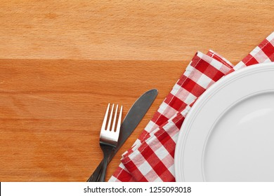 Empty plate and towel over wooden table background.