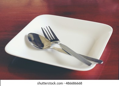 Empty plate with utensils on wooden background.