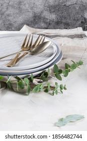 Leere Teller und Besteck als Muster auf einem rustikalen, mit Eukalyptusblättern und Ästen dekorierten Tisch. Top-Geschirr für die Tischdekoration des Küchenchefs und für das Design der Menümarkierung