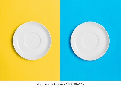 Empty plates on a contrasting yellow and blue background.