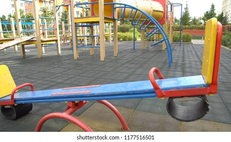 Empty playground in the fall with different equipment and a seesaw. Focus on background