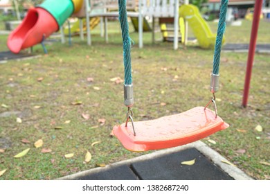 Empty playground swing at a park during evening