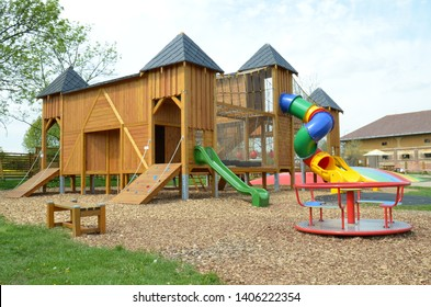 An empty playground wooden castle   playground with slides, merry-go-round, roundabout, and many other playing equipment and activities for small and bigger children.